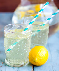 Citrus lemonade in pitcher and glasses on wooden table