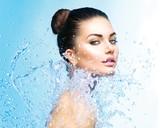Beautiful girl under splash of water over blue background - 65431457