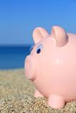 Summer piggy bank on the beach