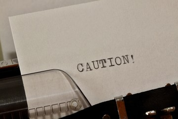 Caution text typed on old black typwriter