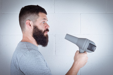 man wipes his beard with hair dryer