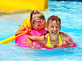 Children in life jacket in swimming pool.