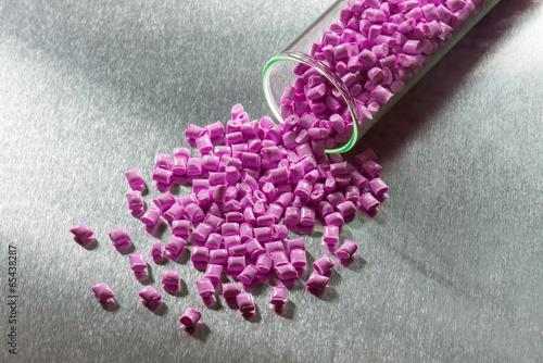Leinwandbild Motiv Plastik Granulat mit Reagenzglas auf Stahlplatte
