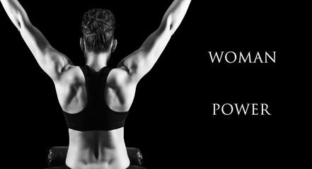Muscular woman bodybuilder posing back over dark background.