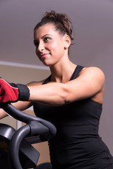 Woman smiling on exercise bicycle in the fitness room.