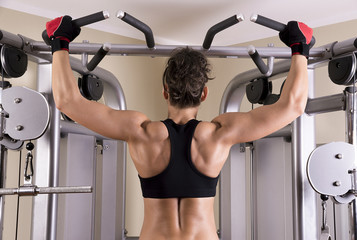 Athletic young woman showing muscles of the back.