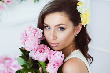 Young Woman in Flowers. Healthy Long Hair and Clean Skin.