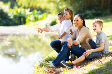 young family sitting by lake