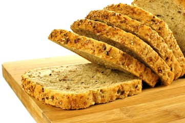 Sliced loaf of bread with grains on wood over white