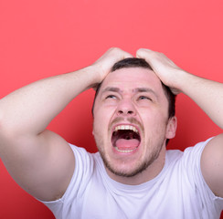 Portrait of angry man screaming and pulling hair against red bac