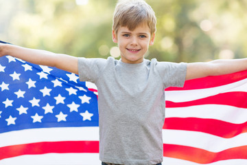 cute little boy holding american flag