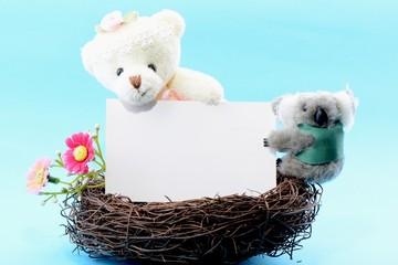 Nest with a blank card and teddy bear and koala