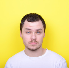 Portrait of man with funny face against yellow background
