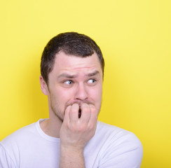 Portrait of man biting nails against yellow background