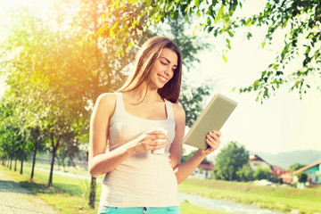 Young woman in park with tablet and takeaway coffee