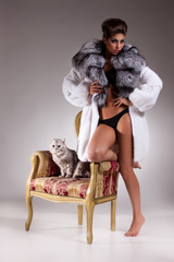 Young Woman In Fur Coat And Cat On Armchair