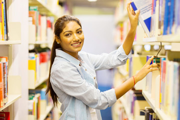 female indian college student pulling a book off shelf