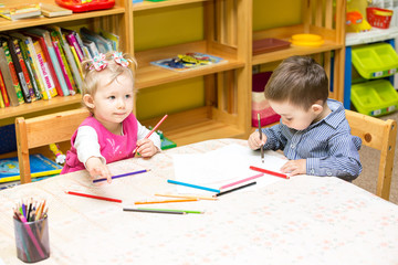 Two little kids drawing with colorful pencils in preschool
