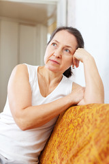 pensive mature woman in home