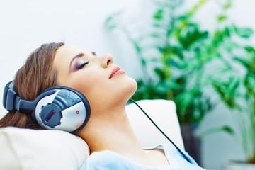Young woman home portrait. Sleeping girl with headphones.