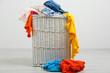 Full laundry basket  on wooden floor on gray background - 65448225