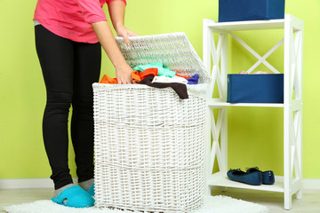 Woman with full laundry basket on home interior background