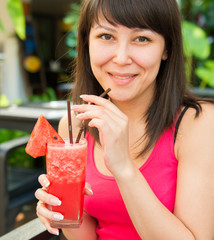 Close-up portrait of young smiling woman with the juice