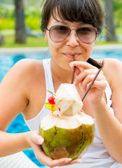 Pretty woman drinking coconut cocktail against outdoor pool