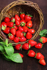 Ripe sweet strawberries in wicker basket on wooden background