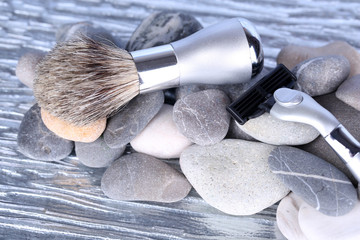 Shaving accessories on stones on bright background