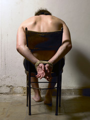 Tortured man on a chair with tied hands