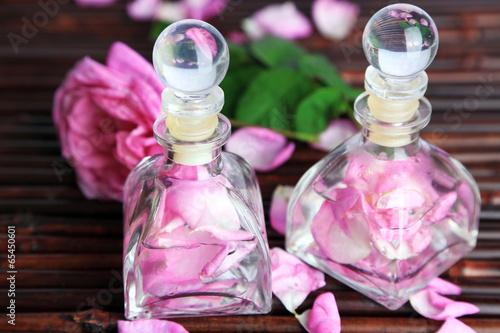 Rose oil in bottles on bamboo mat background