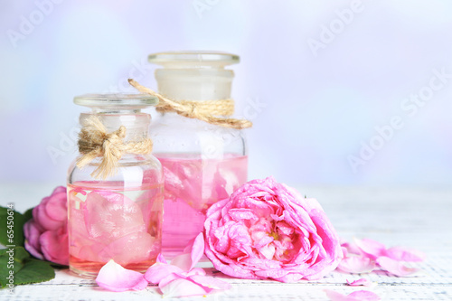 Rose oil in bottles on color wooden table, on light background