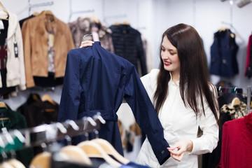 Girl choosing jacket at boutique