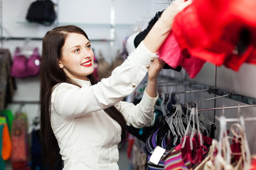 Smiling girl choosing bra at fashion store