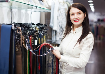 Girl choosing belt at shop