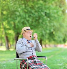 Senior man having an asthma attack in park