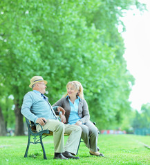 Mature couple talking seated on bench in park