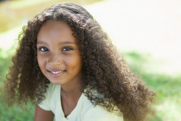 Young girl smiling at the camera in the park