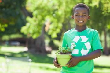 Young boy in recycling tshirt holding potted plant