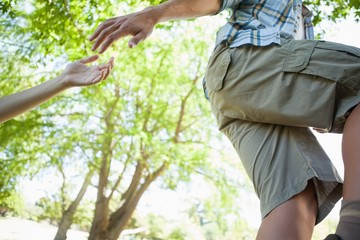 Man giving helping hand to girlfriend on hike