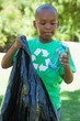Little boy in recycling tshirt picking up trash