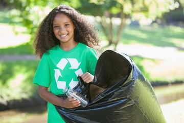 Young environmental activist smiling at the camera picking up tr