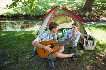 Cute man serenading his girlfriend on camping trip