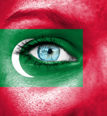 Woman face painted with flag of Maldives