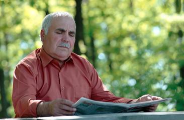 Senior man sitting reading a newspaper