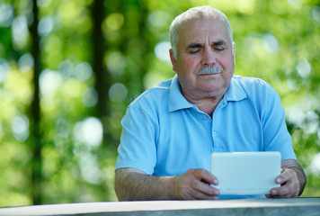 Elderly man reading on a tablet computer