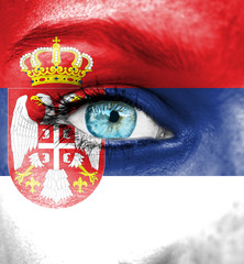 Woman face painted with flag of Serbia