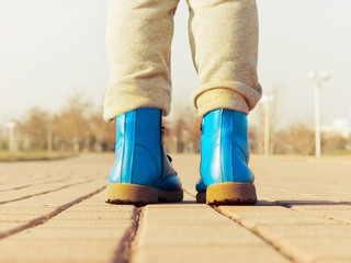 Boots of child walking at park