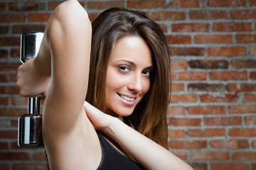 beautiful smiling woman lifting dumbbells on brick background